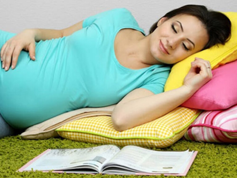 Mẹ bầu nên nằm nghiêng, kê gối ở bụng và chân để giảm đau cột sống.