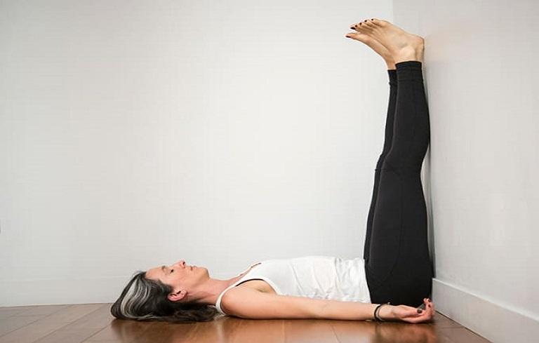 Động tác áp sát chân lên tường giúp giảm đau bụng kinh