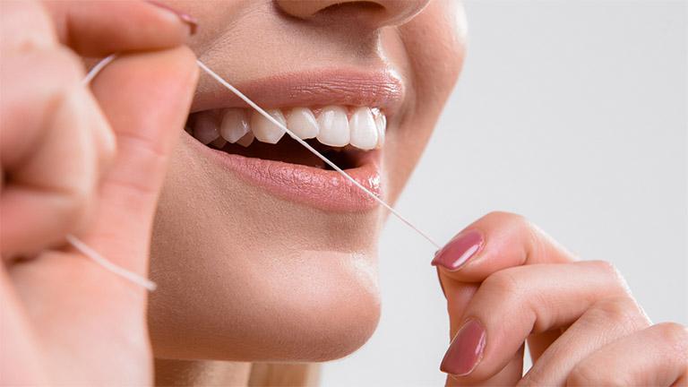 Sử dụng chỉ nha khoa để loại bỏ thức ăn dư thừa trong kẽ răng thay vì sử dụng tăm tre
