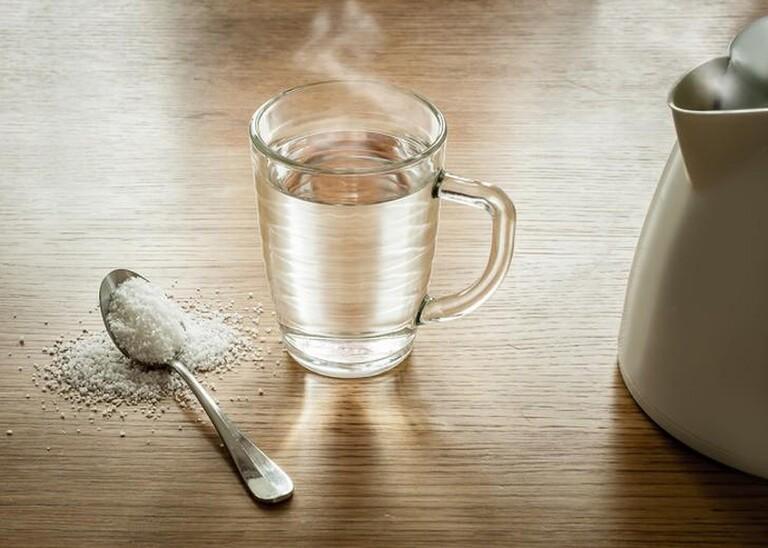 Nước muối ấm ngoài tác dụng sát khuẩn còn giảm ê buốt chân răng.