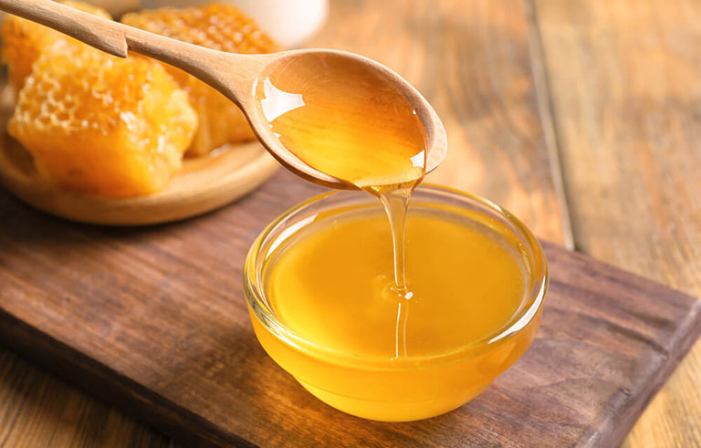 Dùng mật ong nguyên chất bôi lên vùng lợi bị viêm cần điều trị