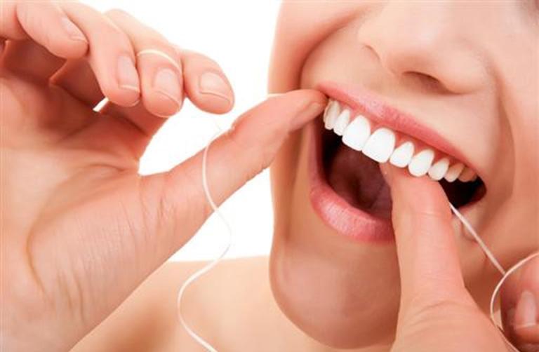 Dùng chỉ nha khoa để loại bỏ thức ăn thừa tồn tại bên trong kẻ răng