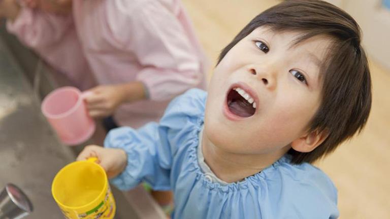 Tập cho trẻ thói quan súc miệng bằng nước muối mỗi ngày 2 lần để làm sạch răng miệng và hỗ trợ phòng ngừa bệnh chuyển biến nặng