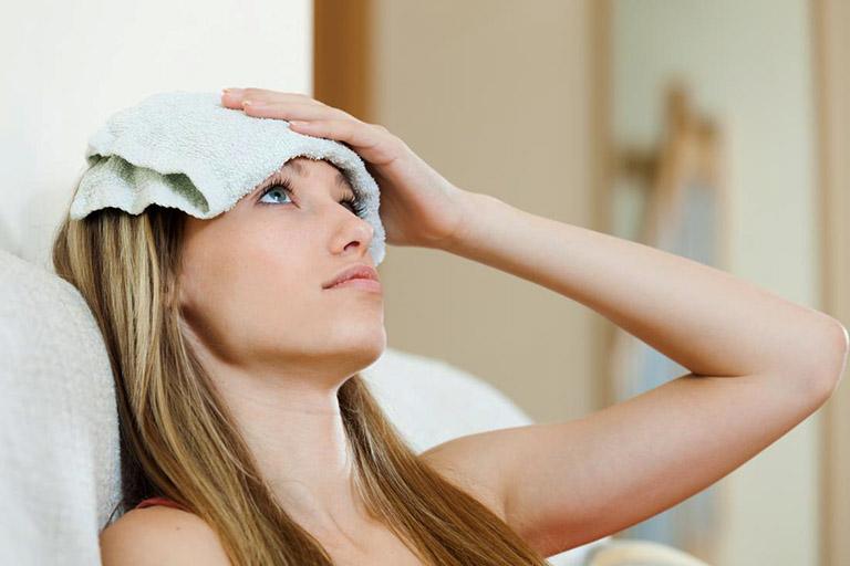 Hạ nhiệt cơ thể bằng cách chườm mát thông qua việc đặt khăn mát lên vùng trán và nằm nghỉ ngơi