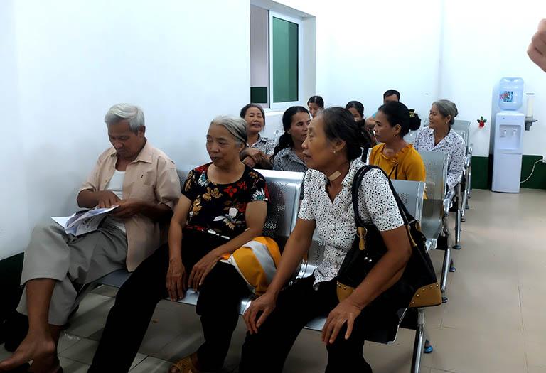 Ông Thoan (bên trái) đang đợi khám bệnh tại bệnh viện Tai Mũi Họng Quân dân 102
